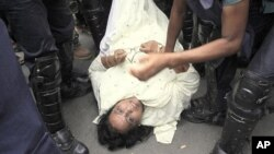 Bangladesh riot police detain an opposition activist, on ground, during a 36-hour strike that began at dawn Sunday in Dhaka, Bangladesh, June 12, 2011