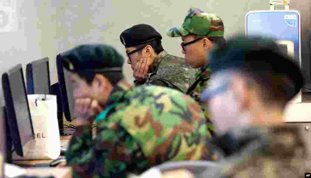 South Korean soldiers monitor computers at the Seoul train station following a report about a possible nuclear test conducted by North Korea, February 12, 2013.