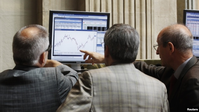 Traders look at a computer screen at the Madrid Bourse, July 24, 2012.