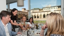 Antoinette Mazzaglia, of Taste Florence, shows tourists how to read a wine label at the Golden View Open Bar overlooking Florence