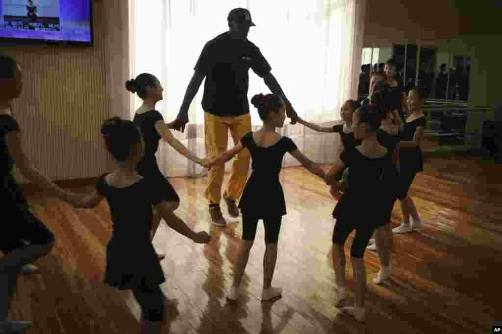 북한을 방문 중인 미국프로농구(NBA) 스타 출신 데니스 로드먼이 15일 평양 만경대 어린이궁전에서 여자아이들과 둥글게 손을 잡고 춤을 추고 있다.