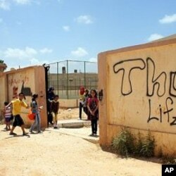 Children play outside their grafitti-covered school yard, closed for months after the uprising, Benghazi (File Photo - June 26, 2011)
