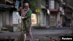 سری نگر میں ایک خاتون کرفیو کے باوجود سڑک پر پڑے پتھروں کی صفائی کر رہی ہے۔