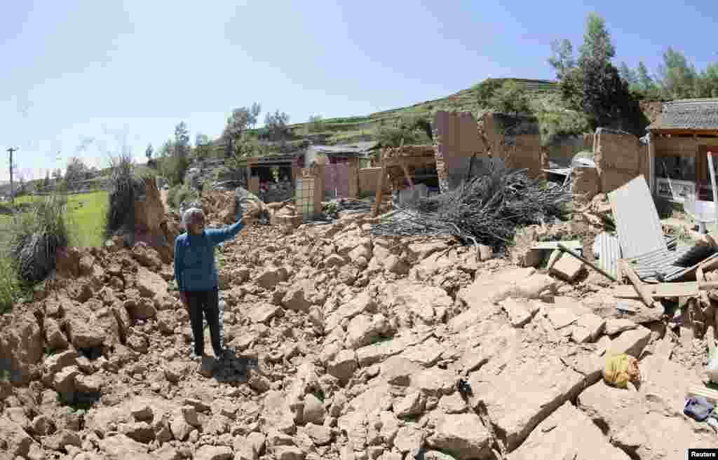 22일 중국 간쑤성 딩시 시에서 규모 6.6 강진이 발생한 가운데, 한 주민이 무너진 주택을 가리키고 있다.