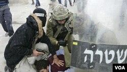 Polisi dan tentara Israel menahan seorang warga Palestina dalam aksi protes di Qalandiya, antara Ramallah and Yerusalem (15/5).