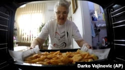 Granny's Kitchen: Jelena Petrovic places the tray with food into the oven