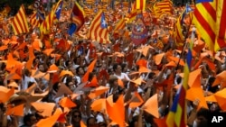 People wave pro-independence Catalan flags,