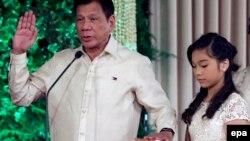 로드리고 두테르테 필리핀 신임 대통령(왼쪽)이 30일 마닐라의 대통령궁에서 딸 베로니카가 들고 있는 성경에 손을 얹은 채 취임 선서를 하고 있다.