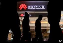 FILE - Pedestrians walk past a Huawei retail shop in Beijing, Dec. 6, 2018.