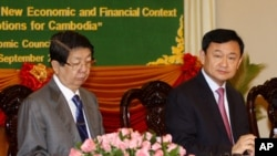 Thaksin Shinawatra, former Thai prime minister, center, sits together with Cambodian Deputy Prime Minister Sok An, left, as Thaksin gives a lecture to Cambodian economists in Phnom Penh, Cambodia, Saturday, Sept. 17, 2011.