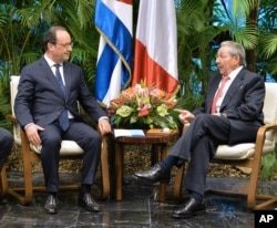 FILE - French President Francois Hollande, left, and Cuban President Raul Castro talk during a meeting at Revolution Palace in Havana, Cuba, May 11, 2015.