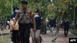 Petugas kepolisian membawa peralatan setelah menyelidiki lokasi ledakan di kawasan Monas, Jakarta, 3 Desember 2019. (Foto: AFP)