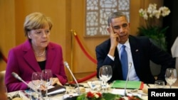 U.S. President Barack Obama and German Chancellor Angela Merkel listen during the G7 Summit working dinner in Brussels June 4, 2014.