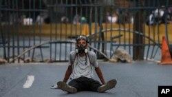 一名反政府抗议者坐在委内瑞拉加拉加斯的路障前(2017年4月24日)
