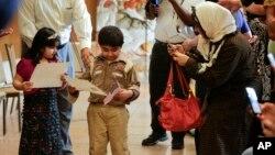 Những công dân mới nhỏ tuổi nhận giấy chứng nhận quốc tịch Hoa Kỳ cùng với cha mẹ tại Sở Di trú Mỹ.