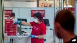 An employee scans coronavirus tests at the airport in Frankfurt, Germany, Friday, Aug. 7, 2020