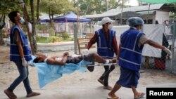 Des agents de santé bénévoles portent un manifestant blessé par balle lors d'une manifestation contre le coup d'État militaire à Mandalay, Myanmar/Birmanie, le 21 mars 2021.