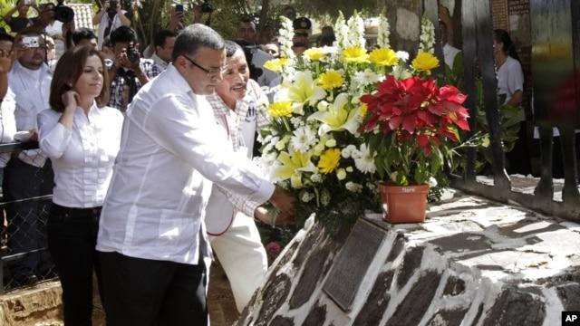 El presidente de El Salvador, Mauricio Funes y un residente de El Mozote, colocan una ofrenda floran en el monumento que honra las víctimas de la masacre que tuvo lugar en 1981.