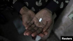 FILE - An AIDS patient holds an anti-retroviral drug used to treat HIV/AIDS.