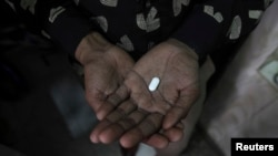 FILE - An HIV patient holds an anti-retroviral drug.