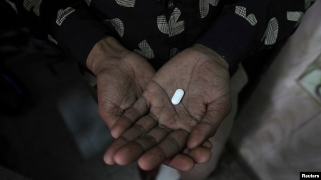 FILE - An AIDS patient in New Delhi, India, holds an anti-infectious drug.