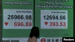 A panel displaying the closing Hang Seng Index and Hang Seng China Enterprise Index are shown outside a bank in Hong Kong, China, June 29, 2015.