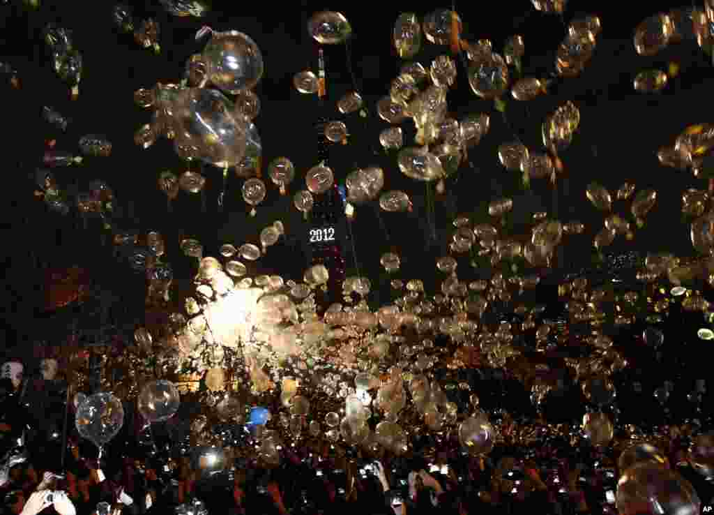 People release balloons as the Tokyo Tower is illuminated to celebrate the New Year at a countdown event at the Zojo-ji Buddhist temple in Tokyo, January 1, 2012. (Reuters)