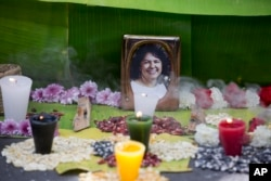 FILE - A picture of Berta Caceres sits on an altar in her honor during a demonstration outside Honduras' embassy in Mexico City, June 15, 2016.