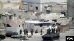 Pasukan Suriah dengan kendaraan bersenjata saat melakukan penyerbuan di Latakia (15/8).