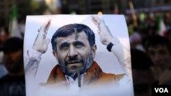 Seorang pendukung Hizbullah di Lebanon memegang poster bergambar Presiden Iran Mahmoud Ahmadinejad.