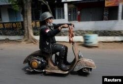 Seorang penggemar ekstrem Vespa mengendarai skuter Vespa setelah mengikuti festival Vespa ekstrem di Semarang, 22 Juli 2018.