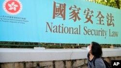 香港一名婦女走過街頭的國安法宣傳牌。 (2020年6月30日)