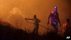 Para relawan dan warga berusaha memadamkan kebakaran hutan yang mendekati kawasan permukiman di Obidos, Portugal, Senin (16/10).