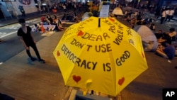 FILE - An umbrella, which has become an icon of the protest, reads pro-democracy messages above the student-led protest site in the Mong Kok district of Hong Kong, Monday, Oct. 20, 2014.