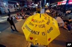 FILE - An umbrella, which has become an icon of the protest, reads pro-democracy messages above the student-led protest site in the Mong Kok district of Hong Kong, Oct. 20, 2014.