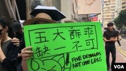"""9-29香港全球反極權大遊行的示威者的示威者,手持畫上連登討論區表情符號""""連豬""""的標語。(攝影: 美國之音湯惠芸)"""