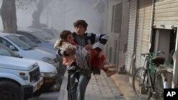 巴基斯坦奎達發生自殺爆炸後幾分鐘,一名受傷少年抱著一名受傷女孩跑向安全地點。