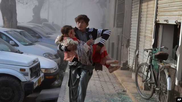 An injured boy carries an injured girl as he runs towards a safe area a few minutes after the suicide bombing in Quetta, Pakistan, Feb. 6, 2016.