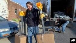 미국 워싱턴 일대 눈폭풍 경보가 내려진 가운데 21일 메릴랜드주 타우슨 시의 공구가게 주인이 눈 치우는 삽을 트럭에서 내리고 있다.