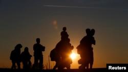 FILE - Sekelompok migran berjalan di sepanjang rel kereta api saat matahari terbenam dekat dengan tempat pengumpulan migran di Roszke, Hungaria 12 September 2015