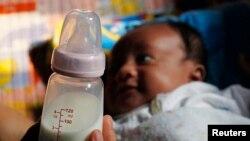 Seorang ibu di Jakarta, tengah memegang botol susu anaknya, 7 Agustus 2012. (Foto: ilustrasi).