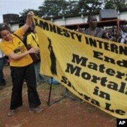 An Amnesty International member unfolds a banner as she prepares for the campaign against maternal deaths in Freetown, Sierra Leone (File Photo)