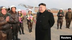 FILE - North Korean leader Kim Jong Un smiles as he provides field guidance to the flight drill of female pilots of pursuit planes of the KPA Air and Anti-Air Force in this undated photo released by North Korea's Korean Central News Agency.