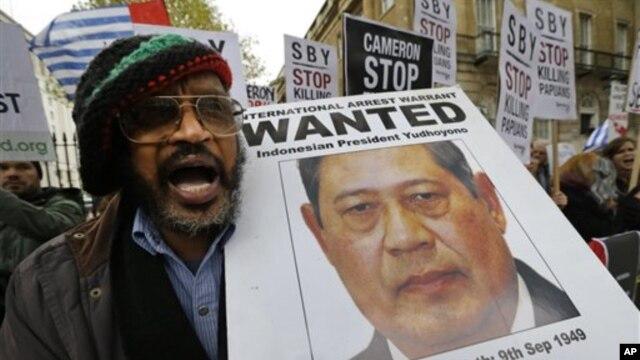 Seorang demonstran memegang gambar Presiden Susilo Bambang Yudhoyono selama unjuk rasa di depan tempat tinggal Perdana Menteri Inggris David Cameron, London. (AP/Lefteris Pitarakis)