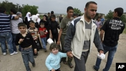 Syrian families carry their belongings as they arrive by foot in Wadi Khaled area, northern Lebanon, near the Lebanese-Syrian border, April 28, 2011