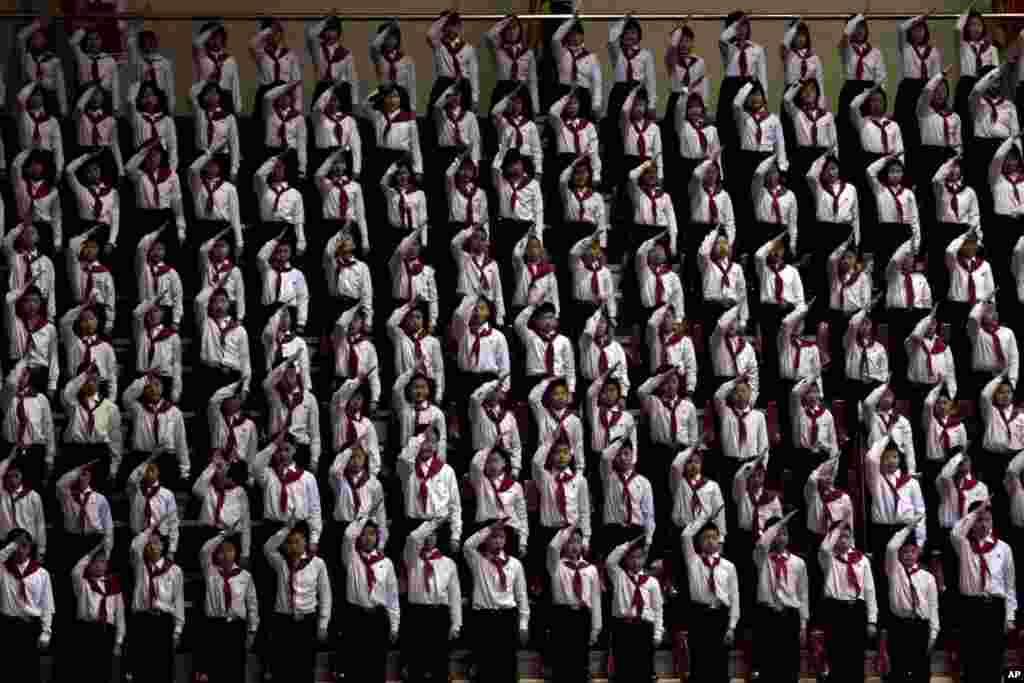 Trẻ em Bắc Triều Tiên đứng xếp hàng và giơ tay chào tại một sân đấu thể thao ở Bình Nhưỡng trong một hội nghị quốc gia của Liên hiệp Thiếu nhi.