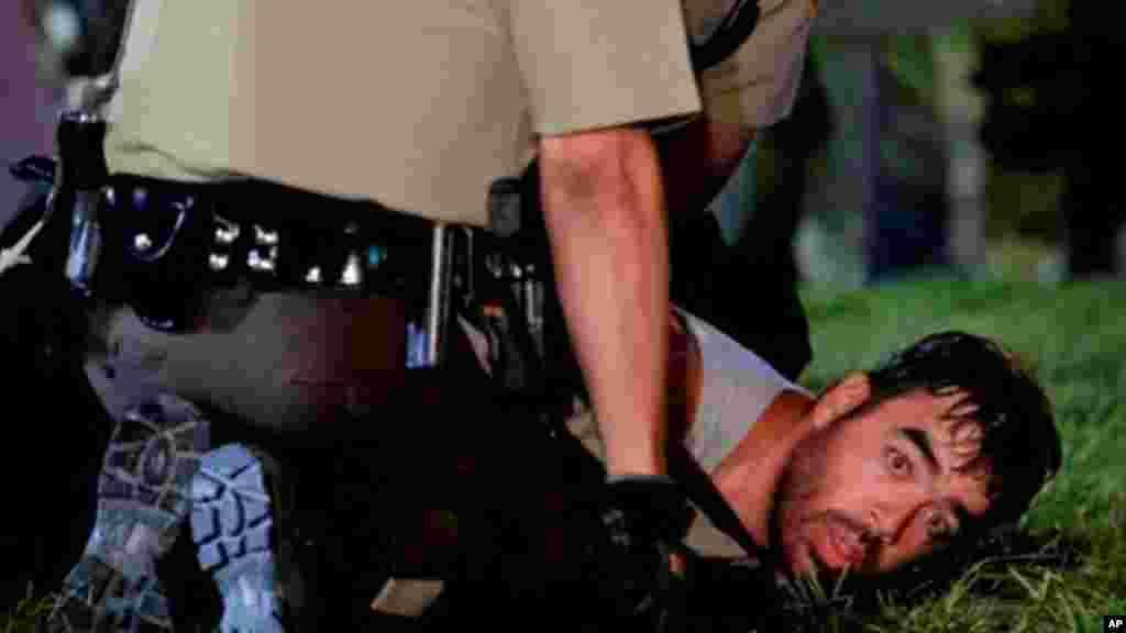 دو مأمور پلیس در حال دستگیری یک تظاهرکننده - فرگوسن، ۲۷ مرداد