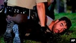 Policijac hapsi učesnika demonstracija u Fergusonu u državi Mizuri, 18. avgust 2014.