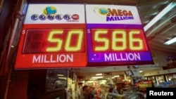 A worker at Nick's Liquor Store sells lottery tickets as a sign shows the Mega Millions jackpot estimated at $586 million in Venice, California, Dec. 16, 2013.