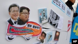 Pictures of South Korean President Moon Jae-in, left, and North Korean leader Kim Jong Un are seen on a sign during a rally to denounce the United States' policy against North Korea and demand the peaceful Winter Olympics in Seoul, South Korea.